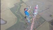 Работник сменя крушка на телевизионна кула с височина 477 метра