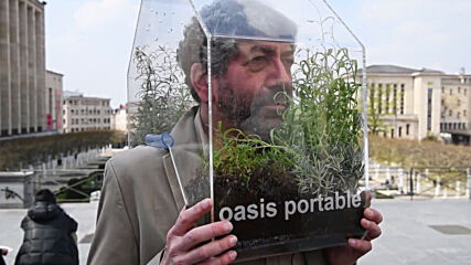 Defended from COVID - Belgian artist wears mini-greenhouse on his shoulders