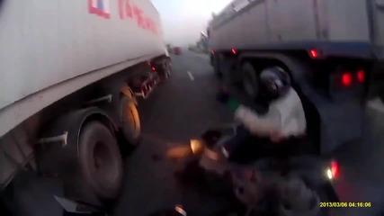 Мъж на скутер се разминава на косъм между два камиона