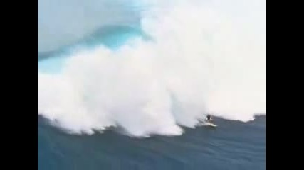 Сърфист сърфира по огромна вълна