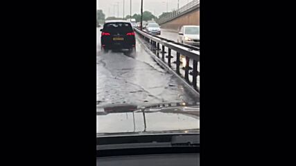 UK: Cars drive on swamped roads in London as thunderstorms bring flash flooding