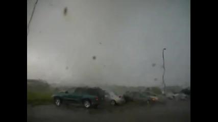 Мъж си говори по телефона, докато покрай него преминава торнадо