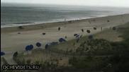 Внезапен вятър на плажа вдига чадърите на туристите във въздуха