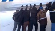 Пътници бутат самолет, за да размразят спирачките му