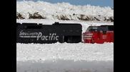 Три дизелови локомотива засядат в огромна пряспа сняг при почистване на релсите