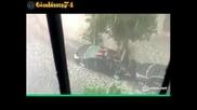 Мъж пази колата си от падащият град,легнал върху нея.