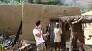 Ловец от африканското племе Догони дава на турист да стреля с неговата стара ловна пушка