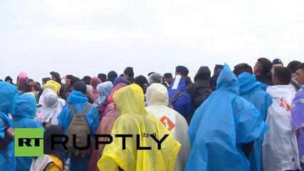 Унгария: Бежанци чакат да се качат на автобуси в проливен дъжд в Рьоске