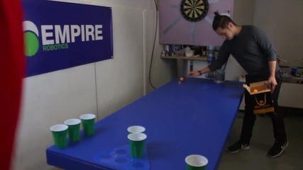 Робот вкарва пинг-понг топчета в бирени чашки