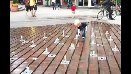 Момченце си играе с атрактивен фонтан.