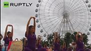 Стотици бременни китайки играят йога за Деня на майката