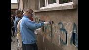 Младежи чистят графити, проповядващи расова и етническа омраза