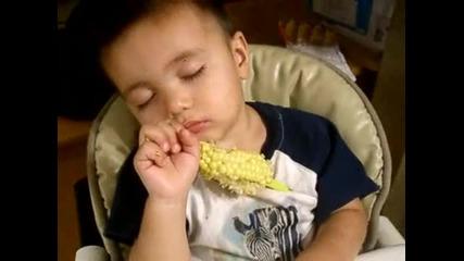 Дете заспива, докато яде царевица