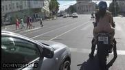 Маце дибидюс голо се вози на мотор по улицата в Русия
