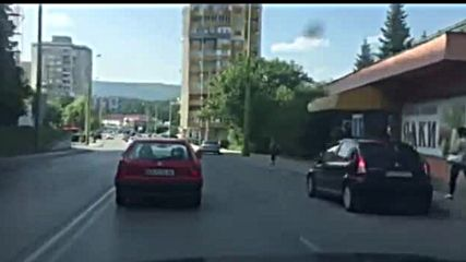 Бебе виси през прозореца на движеща се кола