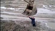 Опитен багерист помага на човек заседнал в калта