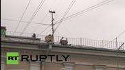 Russia: Daredevil climbs across St. Petesburg street hanging onto telephone wire