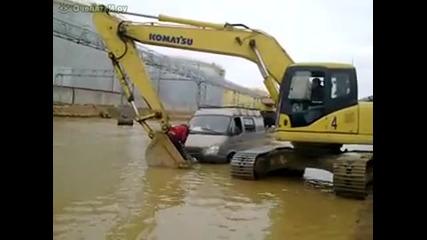 Изобретателен багерист помага на шофьор със закъсал бус в наводнена улица