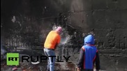 State of Palestine: Student takes axe to West Bank wall amidst clashes