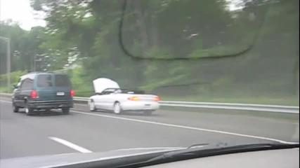 Човек кара кола с вдигнат капак докато чете весник!