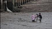 Момче легна в калта за да спаси двама фотографи