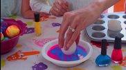 Млада майка с дъщерите си показва как се боядисват великденски яйца с лак за нокти