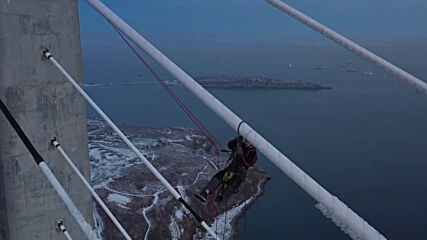 Russia: Alpinist cleans Russky bridge from ice after freezing rain *DRONE FOOTAGE*