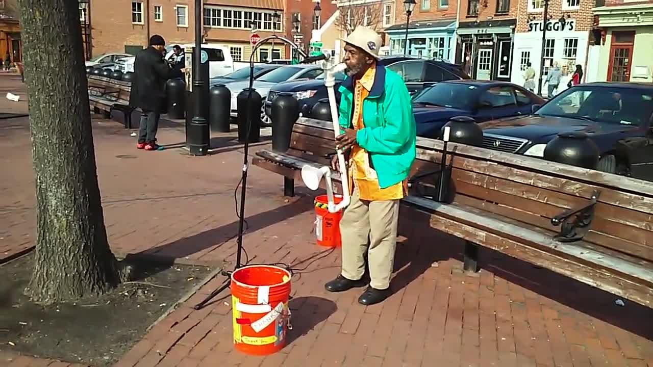 Уличен музикант със саксофон, направен от пластмасови тръби